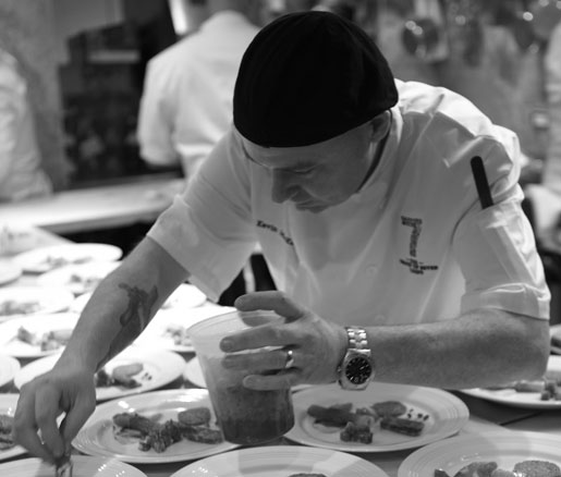A visiting chef plates food in the James Beard House kitchen
