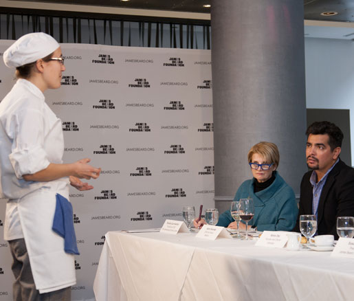 A competitor presents her dish to the judges panel