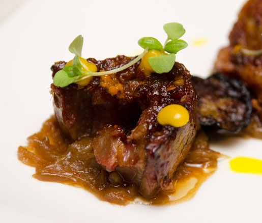 Moroccan barbecued lamb belly with housemade harissa caramelized onions, Japanese eggplant, and orange curd