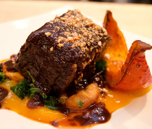 Avocado Leaf–Roasted Short Ribs with Spiced Red Kuri Squash, Masa Dumplings, Heirloom Kale con Plátanos, Cotija Cheese, and Red Wine–Cola Mole