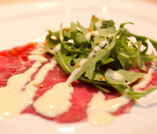Northwest-Raised Certified Angus Beef® Carpaccio with Arugula, Soft-Boiled Duck Egg Sauce, Oregon Buckwheat Honey, and Bee Pollen