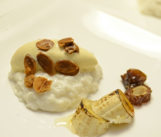 Coconut Rice Pudding with Brûléed Bananas, Dates, Rum Glaze, Candied Almonds, and Ginger Ice Cream