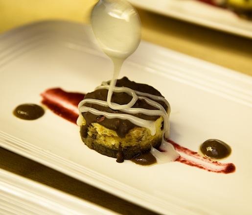 Cinna-Bun Cheesecake with Cinnamon–Graham Cracker Crust, Cherry Pop Rock–Chocolate Ganache, Raisin Sauce, and Vanilla Glaze