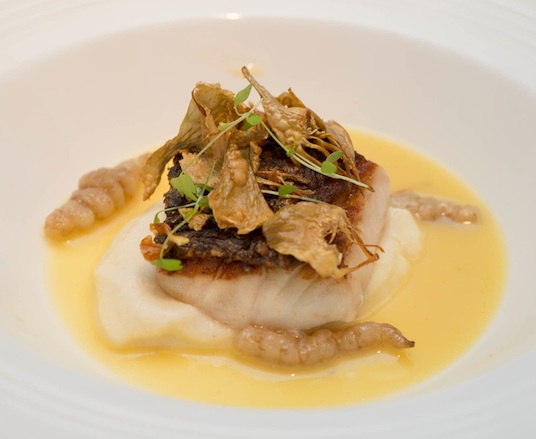 Wild Black Bass with Celeriac Purée, Crosnes, Olive Oil–Poached Artichokes, and Mussel–Saffron Fumé​