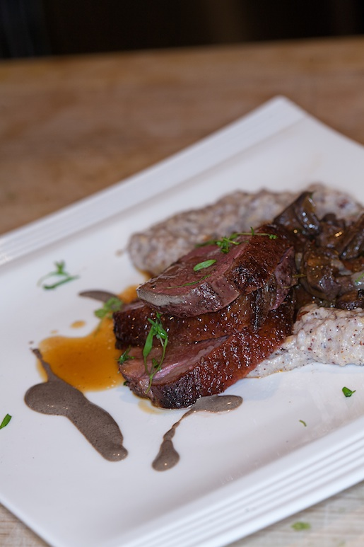 Hudson Valley Duck Duo > Creole-Seasoned and Seared Breast with Satsuma Jus; and Braised Heart with Story Farms Indian Corn Grits, Foraged Black Trumpet Mushrooms, and Black Garlic Emulsion
