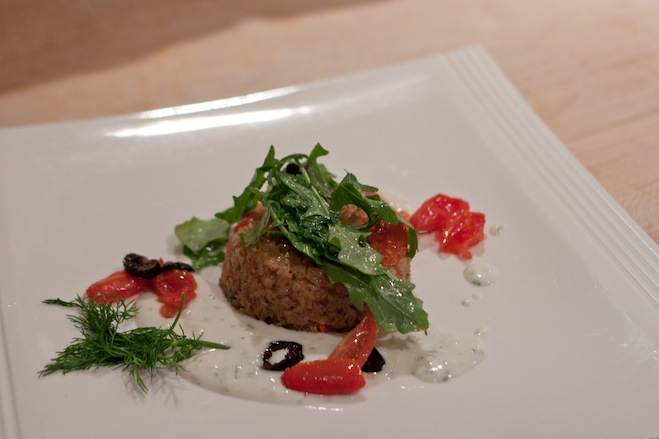 Warm Farro Sformatino with Cherry Tomatoes, Capers, Black Olives, Mozzarella, Arugula, and Velvet Yogurt Sauce