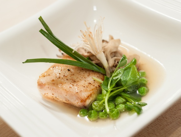 Wild Alaskan Halibut with Potato–Endive Fondue, English Peas, Hedgehog Mushrooms, Lemongrass-Scented Carrot Broth, and Leek–Pea Tendril Salad