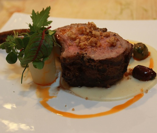 Walnut-Smoked Rack of Lamb with Preserved Lemon–Stuffed Olives, Pecorino Toscano Fonduta, and Winter Mint