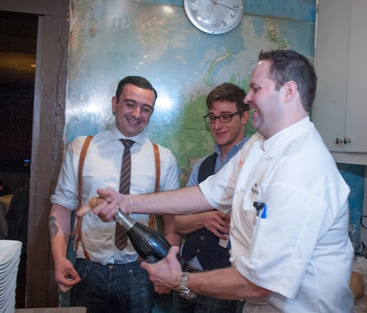 Chef Jason Tilmann opens a bottle of champagne with cocktail expert Theo Lieberman