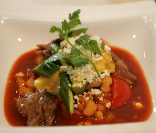 Lamb Neck Posole with Heirloom Tomatoes, Summer Squash, Hominy, Guajillo Pepper Broth, and Queso Fresco