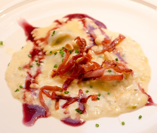 Ligurian-Style Rabbit and Borage Ravioli with Thyme–Leek Sauce, Pine Nuts, Crispy Speck, and Barbera d'Alba Reduction