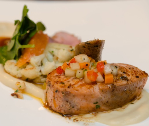 Wine Country Duo > Red Sumac–Seared Skuna Bay Craft Raised Salmon with Pear–Lemongrass Vinaigrette, and Roasted Duck Breast with Duck Bratwurst, Fried Chanterelles, and Cara Cara Orange–Accented Cauliflower
