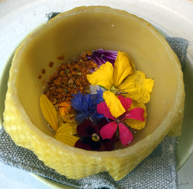 Wax broth with bee pollen and wild flowers, served in a beeswax bowl from Noma's 2018 vegetable menu.