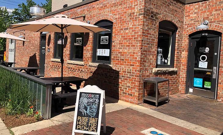 Miss Kim's outdoor dining set up with picnic tables and umbrellas and a chalkboard asking patrons to wear a mask photo by Katie Jozwiak