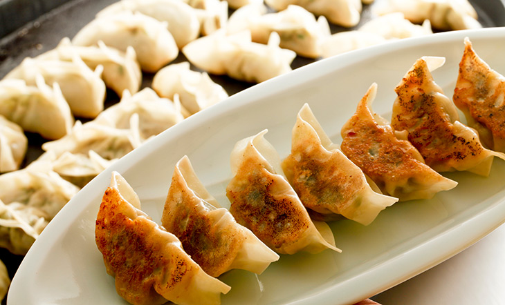 Stock image of pan-fried dumplings with uncooked dumplings in the background