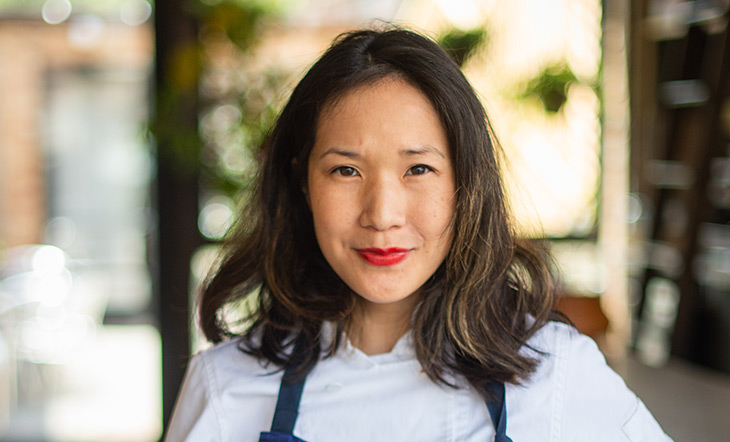 James Beard Award winner Beverly Kim in a white shirt and blue apron photo by Cory Dewald