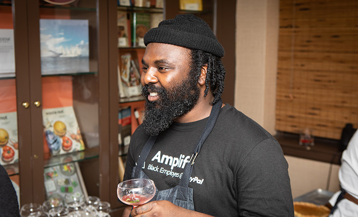 Chef Omar Tate in the front room of the James Beard House holding a drink in his hand photo by Clay Williams