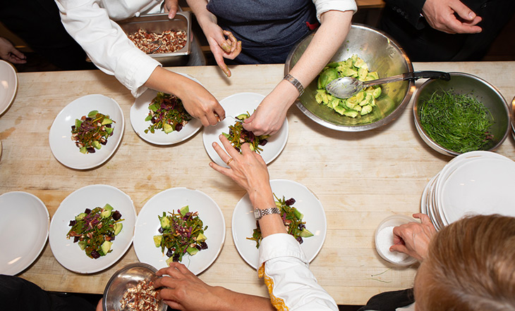 Pati Jinich dinner at the James Beard House, multiple women's hands plating a dish on a butcher block counter photo by Clay Williams