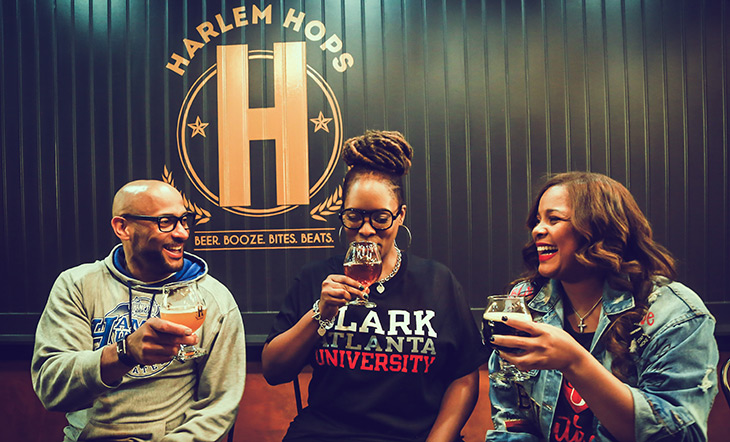 Harlem Hops founders seated at the bar with drinks photo by KUU Photography