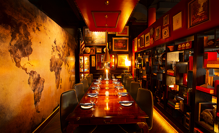Interior shot of the private dining room at The Consulate restaurant. The left hand wall is decorated with a world map while the rest of the room is decorated with various framed images on the wall