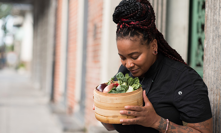 Myisha Mastersson in black chef's jacket holding and looking at steamer basket of vegetables photo by Kayla Madden Photography