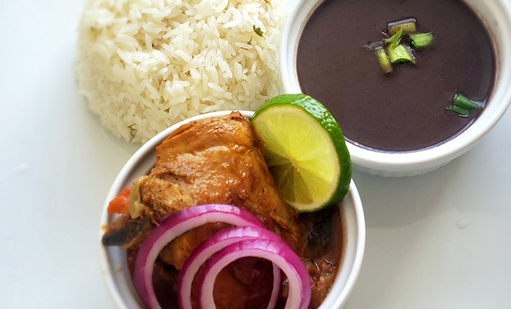 Chicken stew in a white container with a cup of soupy beans and a mound of rice on the side photo by Fritz Edmonis