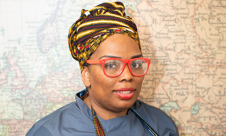 Photo of Adrian Lipscome wearing a headwrap and red glasses at the James Beard House in NYC.