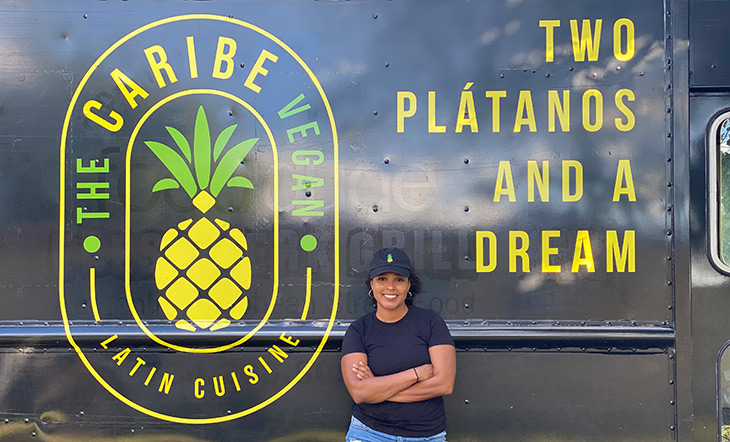 Melissa Guzman leaning against her food truck with The Caribe Vegan logo photo by Melissa Guzman