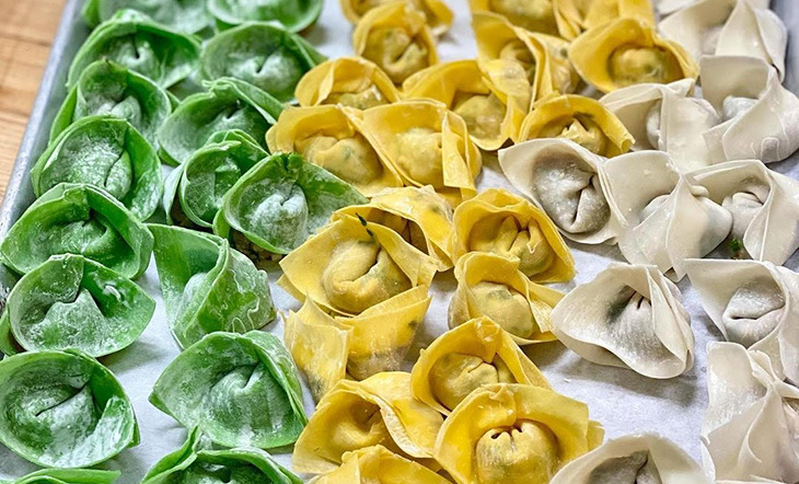 Green, yellow, and tan wontons on a sheet tray photo High Street Hospitality
