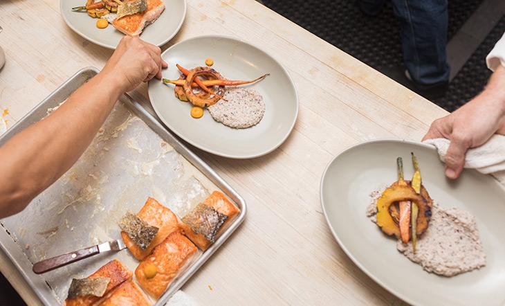 Hands plating salmon at Beard House