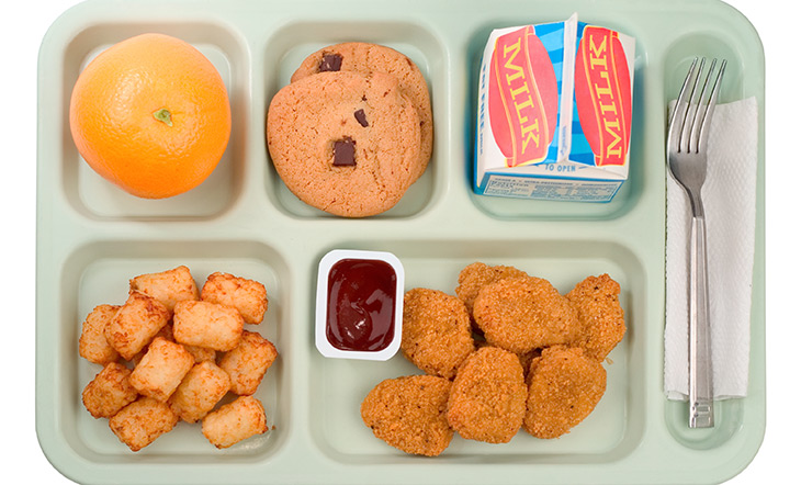 Top down image of school cafeteria tray with chicken nuggets and milk