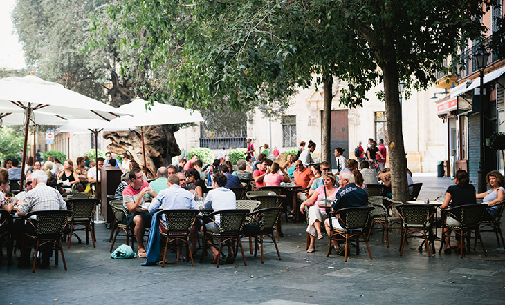 Outdoor tables at a restaurant with groups of people eating and talking