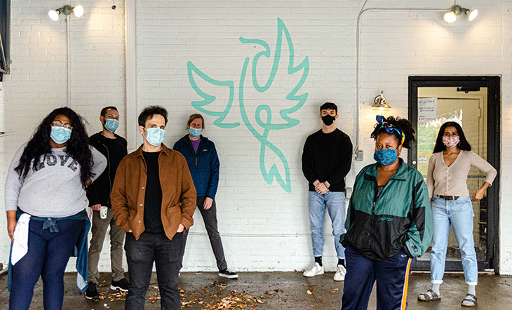 Phoenix Coffee employees in front of a wall painted with a phoenix symbol photo by Brian Johnson