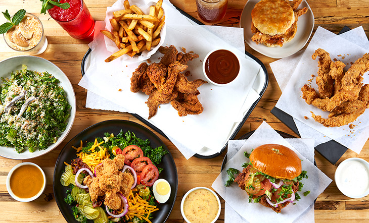 A spread of food on a wooden table , some on trays, some in black and white bowls. There are green salads, chicken tenders, French fries, two different types of chicken sandwiches, a red drink, a tan drink, and three different color sauces in separate white little bowls. Photo by  Kevin Marple