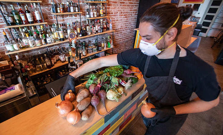 Diaz shows a selection of reclaimed produce displayed on a bar top, including yellow onions, russet potatoes, beets, kohlrabi, and more.