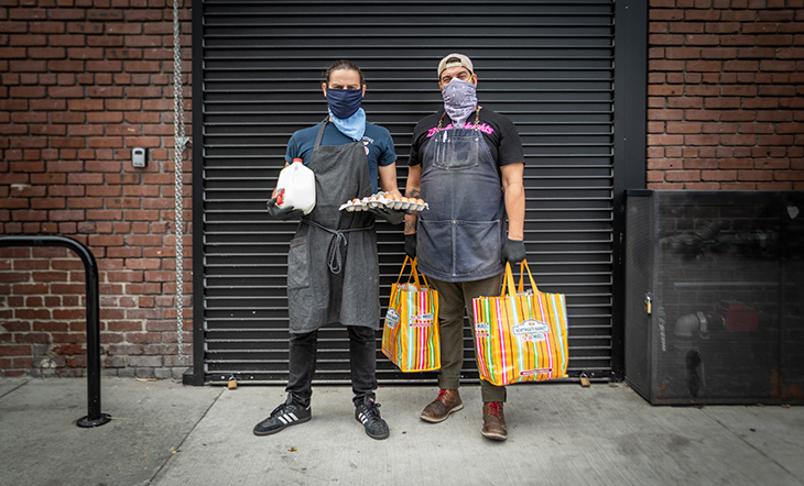 Diaz and Nolasco stand in front of a garage door. Diaz holds a tray of eggs and a gallon of milk. Nolasco holds two multi-colored bags of food.