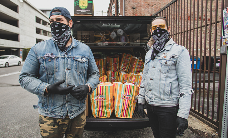 Diaz and Nolasco stand in front of the open trunk of an SUV, filled with multi-colored bags of food to give away.