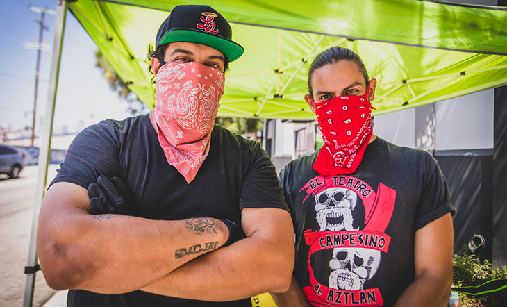 Othón Nolasco and Damián Diaz face the camera, standing under a green tent for their food dispensary.